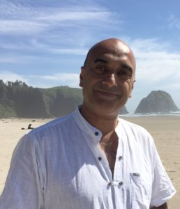 Dr. Avtar Roopra on a beach with cliffs in the background.