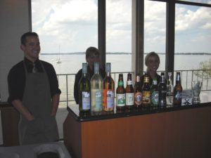 Bartenders stand behind the bar with the lake in the background