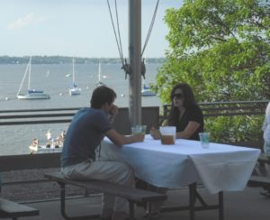 Two people eat at a picnic table with the lake in the background
