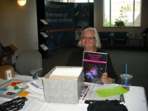 At the registration table, a woman holds up a book titled Cellular and Network Functions in the Spinal Cord
