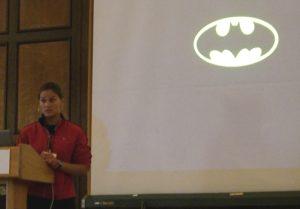 Speaker Liz presents a powerpoint slide with the Batman logo.