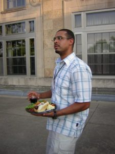 A man poses with a plate full of food and a drink in his hand.
