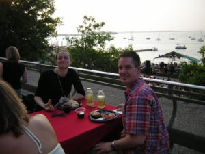 People pose at tables on the Terrace. Lake Mendota is in the background.