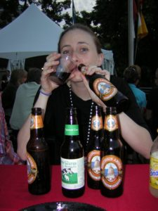 A woman shows off a collection of beer bottles