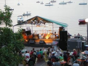 People gather on the Memorial Terrace while a band sets up. Boats are on the lake in the background.