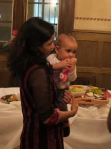 A woman holds an infant near the buffet table, Holiday Party 2017.