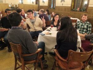 Party-goers sit around multiple tables during the 2017 Holiday Party. One person holds up the peace sign.
