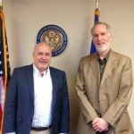 Dr. Meyer Jackson stands beside Congressman Mark Pocan. The crest for the House of Representatives is in the background, along with an American Flag.